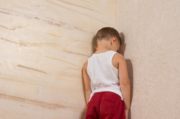 Little young boy wearing white shirt and red pants facing wooden wall