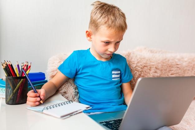 Маленький молодой школьник, работающий дома с ноутбуком, и классные заметки, обучающиеся в виртуальном классе. дистанционное образование и обучение, электронное обучение, концепция онлайн-обучения во время карантина