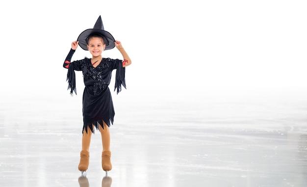 Маленький молодой фигурист позирует в костюме ведьмы хэллоуина на ледовой арене на белом фоне