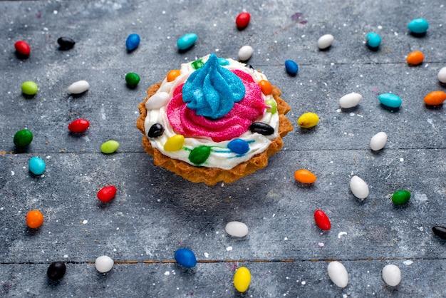 Piccola torta gustosa con crema e diverse caramelle colorate dappertutto, foto di torta color zucchero candito dolce