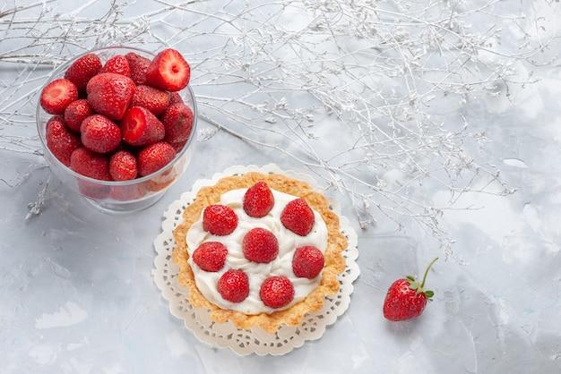 Piccola torta gustosa con panna e fragole rosse fresche sulla scrivania bianca, crema di biscotti ai frutti di bosco