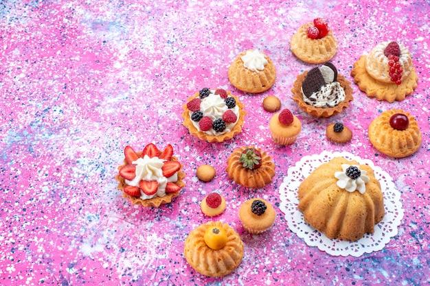 Маленькие вкусные пирожные со сливками вместе с разными ягодами на свету, бисквитный ягодный сладкий запеканный чай