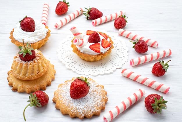 Маленькие вкусные пирожные со сливками и нарезанной клубникой, конфеты на белом, пирожное ягодное сладкое, сахарная выпечка