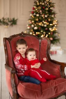 小さな兄は、クリスマスツリーの近くの赤いレトロな椅子で妹を抱きしめます。愛の抱擁、人々の休日を楽しんでいます。一体感の概念。