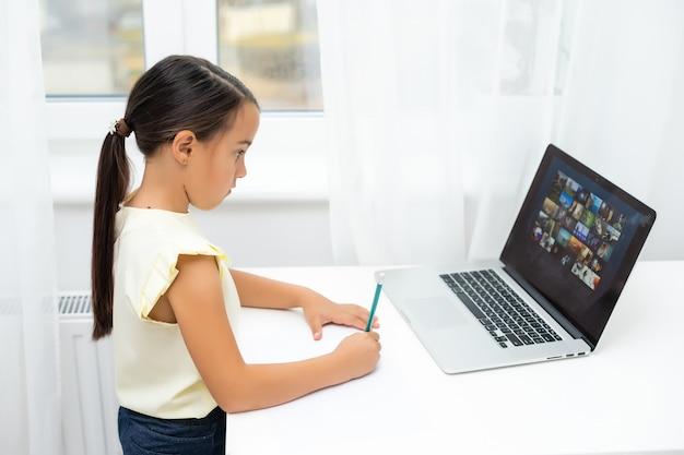 驚きと興奮の表情でノートパソコンの画面を見ている小さな女の子。メモを取るスマートな、微笑む少女。ビジネスコンセプトにおけるコミュニケーション。