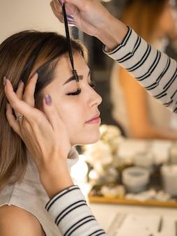 Живой за кулисами визажист красит бровь молодой женщины кистью возле зеркала.