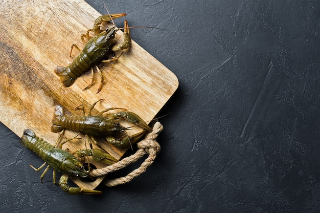 Live crayfish run away from the wooden chopping board.