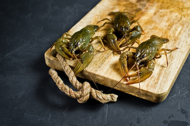 Live crayfish on a wooden chopping board.