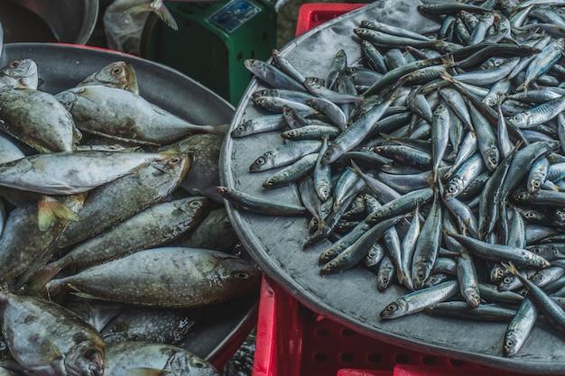 Живая рыба на тарелке, люди покупают и продают морепродукты и овощи на уличном продовольственном рынке в ази ...