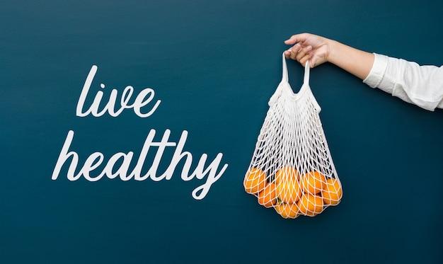 庭から新鮮なオレンジを保持している女性と健康的な概念を生きる