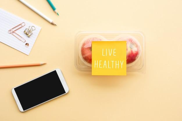 机の上のパッケージにテキストノートと赤いリンゴで健康的な概念を生きる