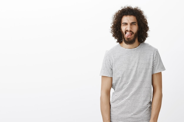 Live life to fullest. portrait of carefree handsome male with beard and curly hair, sticking out tongue and winking