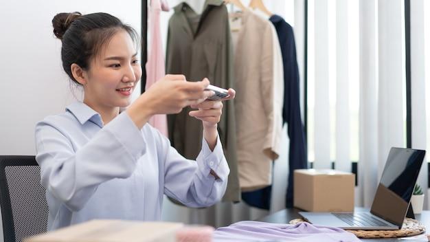Концепция живых покупок онлайн-продавец женского пола, делающий фотографию ткани, которая является продуктом в ее интернет-магазине.