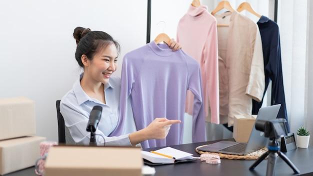 Концепция живых покупок: женщина-продавец разговаривает с онлайн-покупателями, демонстрируя товар через распродажу в прямом эфире перед камерой.
