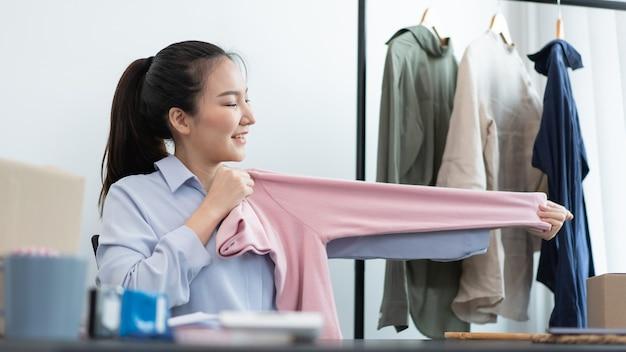 ライブショッピングのコンセプトは、オンライン顧客に対する製品のサイズ比を示す女性トレーダーです。