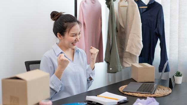Live shopping concept a female seller feeling delighted to her success after the sale reaching the goal.