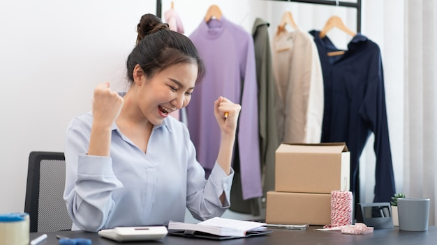 Live shopping concept a female seller feeling glad to her success after the sale reaching the goal.