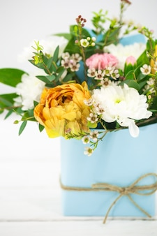 Live spring flowers on a white in a blue pot with bow