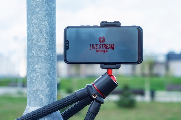 Live strream and subscribe to internet channel on the smartphone display on a flexible tripod. outdoor travel equipment.