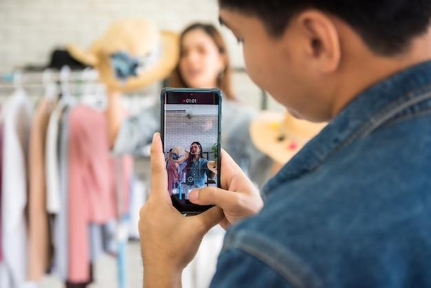 女性のファッションブロガーやスタジオで人気のスタイリストのインフルエンサーガールが帽子とドレスを販売するためにスマートフォンでライブビデオストリーミング。彼女のオンラインブログチャネルの意見リーダーの傾向。売り手の新しい通常。