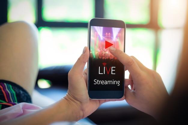 ライブビデオストリーミングの概念。携帯電話を保持している女性の手