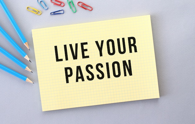 Live your passion text in notebook on gray background next to pencils and paper clips.