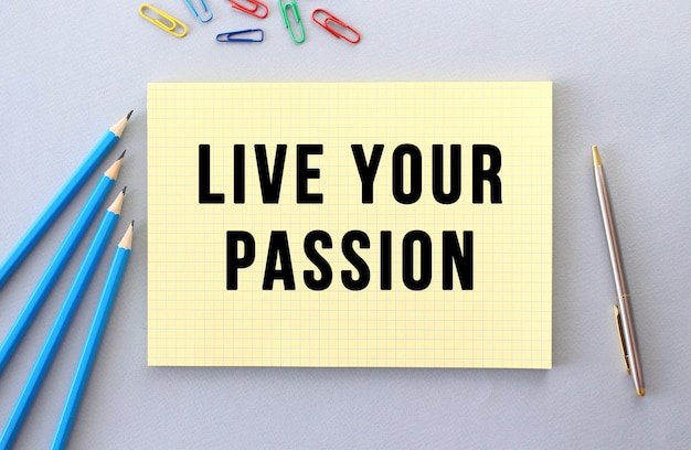 Live your passion text in notebook on gray background next to pencils, pen and paper clips