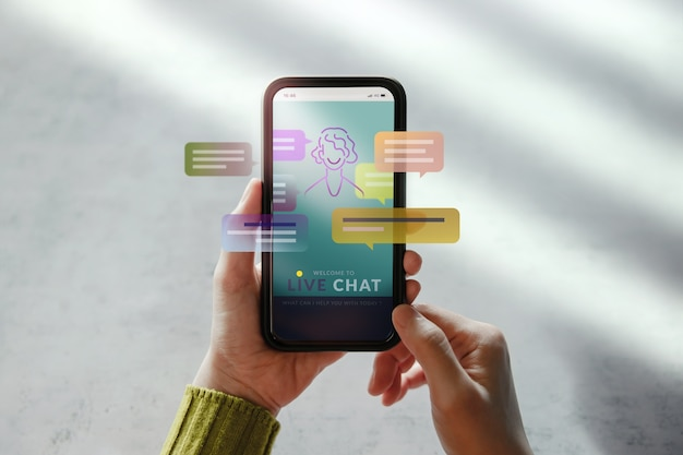 Livechatテクノロジーコンセプト。携帯電話を使用して人工知能と会話するお客様。カスタマーサポート情報のためのバーチャルアシスタント