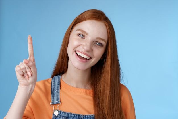 活気に満ちた活気に満ちた幸せな笑顔のヘップフル赤毛の女性の同僚があなたに素晴らしいプロモポインティング人差し指をニヤリと見せてクールな製品を紹介する青い背景を試してみることをお勧めします