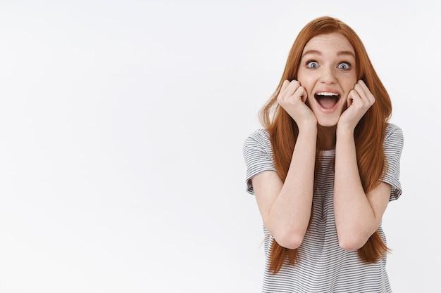 活気に満ちたスリル満点の幸せな若いかわいい赤毛の女の子が青い目を飛び出して驚いて叫び声を上げて元気に興奮しているお気に入りの人気歌手が立っている白い壁を見て驚いて、素晴らしいコンサートに参加してください