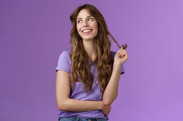 Lively arrogant good-looking girl curly stylish haircut look away dreamy delighted daydreaming thoughtful gaze away touch hair strand rolling curly smiling broadly stand purple background. lifestyle.