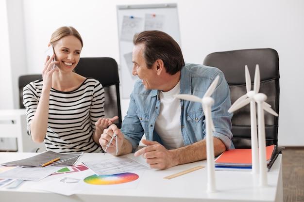 활발한 커뮤니케이션. 풍력 터빈 건설 프로젝트에서 작업하는 동안 쾌활한 전문 엔지니어가 이야기하고 테이블에 앉아