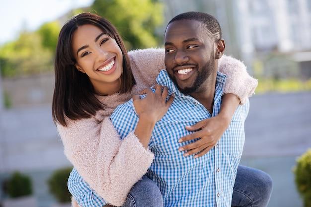 Живой творческий романтический мужчина веселится на улице со своей девушкой, когда она прыгает ему на спину и крепко его обнимает