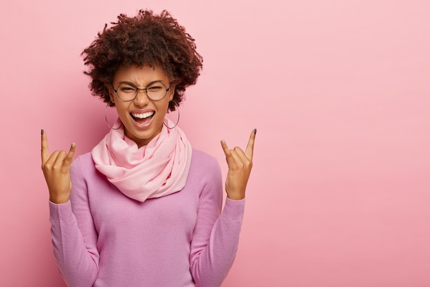 Lively dark skinned young lady makes rock n roll or heavy metal gesture, feels energized, smiles happily, wears glasses and purple poloneck, isolated over pink background