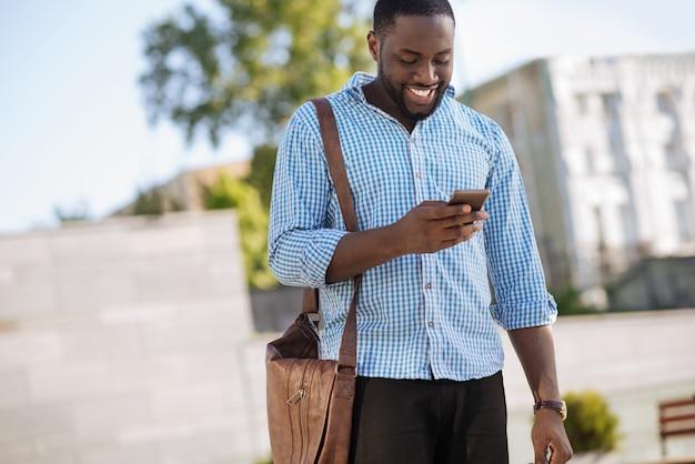 Живой и преданный любопытный парень обновляет свой профиль в социальных сетях и читает сообщения от друзей, используя свой смартфон.