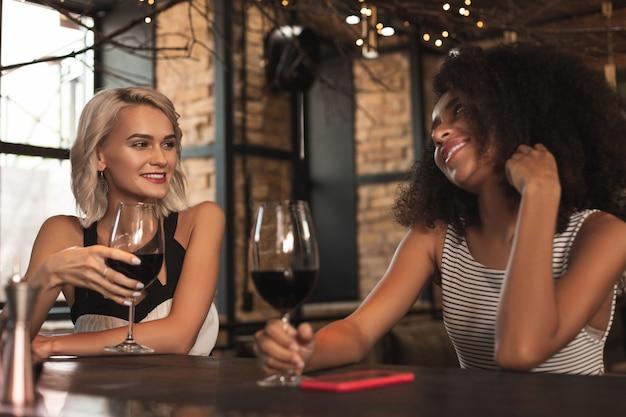 活発な議論。バーカウンターに座って笑顔を交わしながらワインを飲みながらおしゃべりする魅力的な女性友達