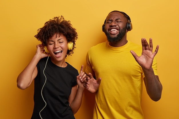 Lively energetic dark skinned couple dance and have fun together, listen different types of music in headphones isolated on bright background.