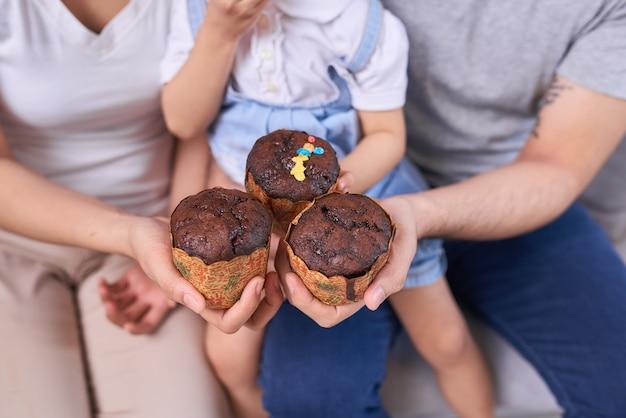 自宅の居間でカップケーキを食べる元気な家族