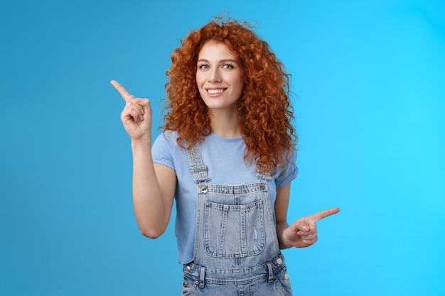 活気に満ちた楽しい25代の赤毛の縮れ毛の生意気な女の子の夏のポジティブな気分のダンスのオーバーオールは、右手の人差し指を横向きに向けて、プロモーションストアのリンクを笑顔で笑っています。