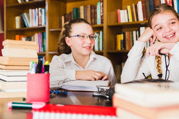 Lively little girls sitting at library desk