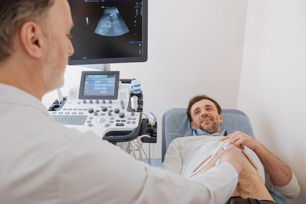 환자가 앞에있는 의료용 침대에 누워있는 동안 초음파 장비를 사용하여 활기차고 유쾌하게 훈련 된 전문 스캔 환자 장기