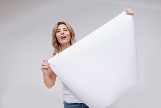Lively and positive. inspiring joyful magnetic lady looking full of hope while posing with a blank poster and standing