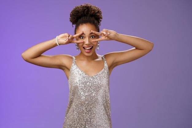 銀色の光沢のあるスタイリッシュなドレスを着た活気に満ちたポジティブな笑顔のアフリカ系アメリカ人女性は、楽しいパーティーを楽しんでいます。
