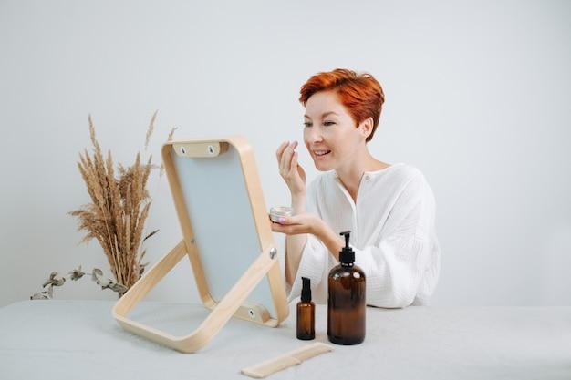 Живая коротковолосая женщина смотрит в зеркало в деревянной раме, нанося консилер. использование экологически чистых продуктов и вещей.