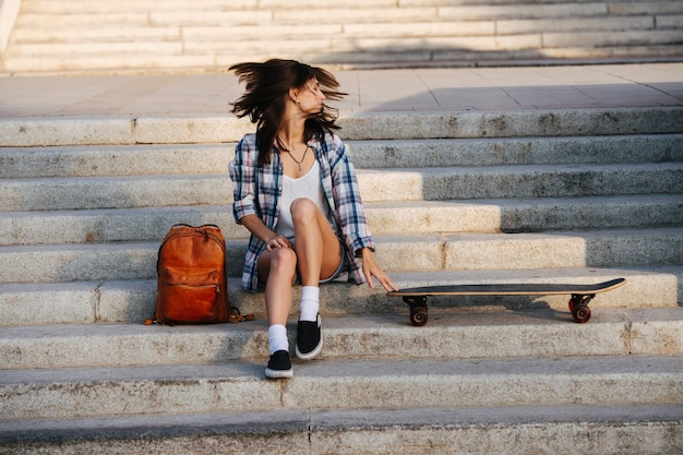Lively woman sitting on the stairs next to her skateboard shaking head