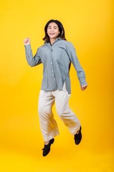 カジュアルな長袖シャツとズボンを身に着けている活気のある若いアジアの女の子は、面白いジャンプアップとダンスのエキサイティングな遊びを楽しんでストレッチし、カットアウトポートレートで健康リフレッシュショーのための簡単な運動をします