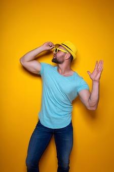 밝은 파란색 셔츠 청바지와 스튜디오 터치에 서 있는 노란색 세련된 모자를 쓴 활기찬 젊은 수염...