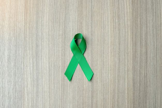 Liver cancer awareness, green ribbon on wooden background