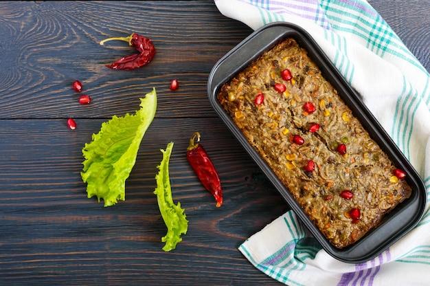 レバーキャセロール。肝臓からの便利な料理。木製のテーブルにご飯と野菜を添えた焼きたての豚レバーのスフレ。上面図。
