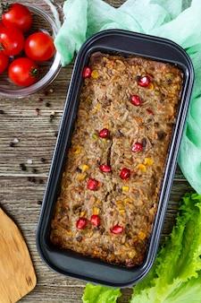 간 캐서롤. 간에서 유용한 요리. 나무 테이블에 쌀과 야채와 함께 갓 구운 돼지 간 수플레. 평면도.